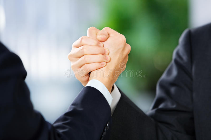 Two businessman grasp each other hand stock image