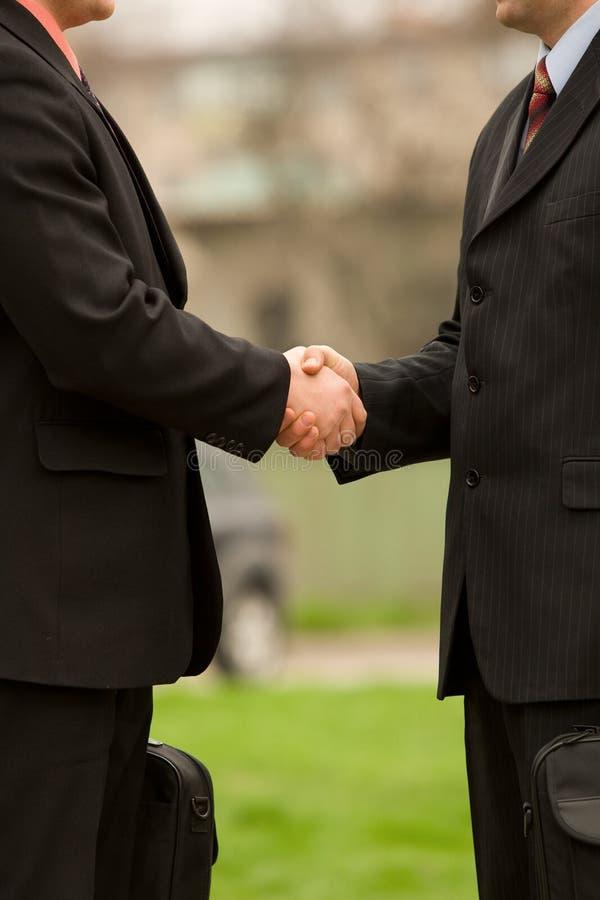 Two businessman handshake. Outdoors scene stock image