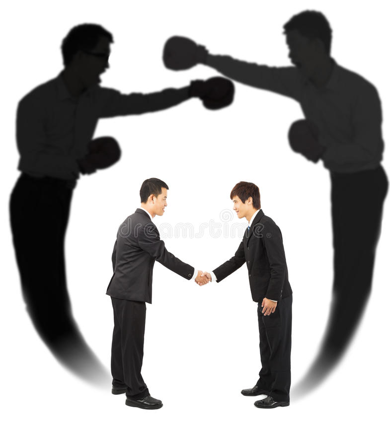 Two businessman handshake with fighting shadow stock photo