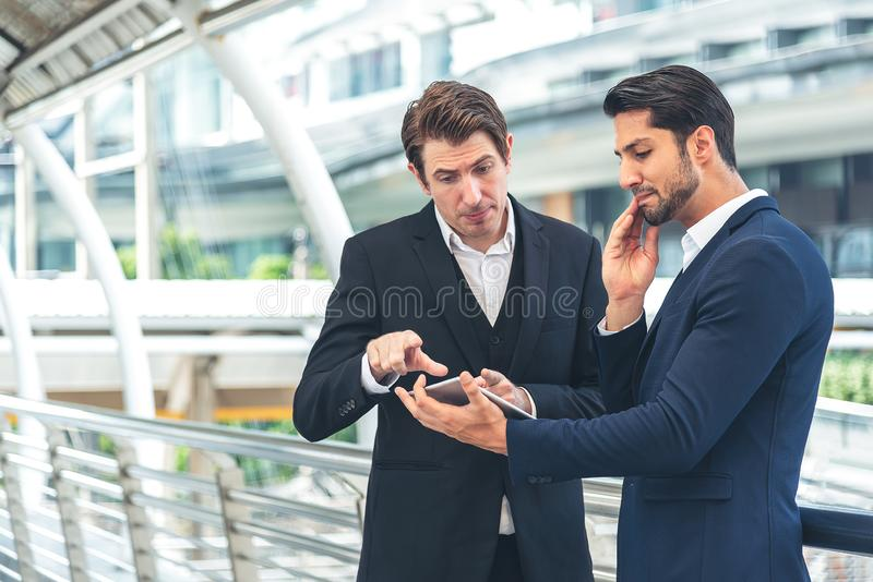 Two businessman holding a tablet seriously having a work discussion outdoor. Young businessman asking for manger opinion royalty free stock image