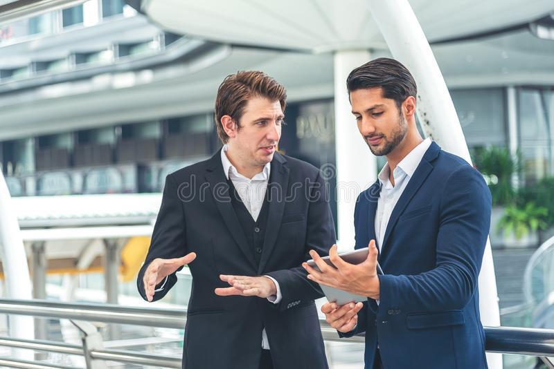 Two businessman holding a tablet seriously having a work discussion outdoor. Young businessman asking for manger opinion royalty free stock photos