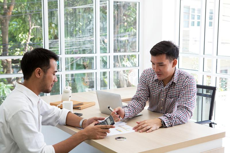 Two businessman plaining data at meeting. Business people meeting around desk. asian people. brainstorming of business. Calculator on the hands of male royalty free stock photo