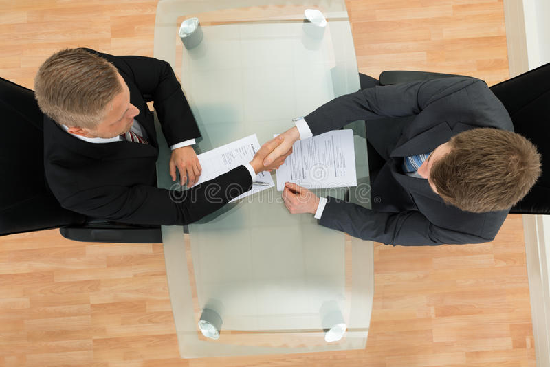 Two businessman shaking hands. Elevated View Of Two Businessman Shaking Hands In The Office royalty free stock photo