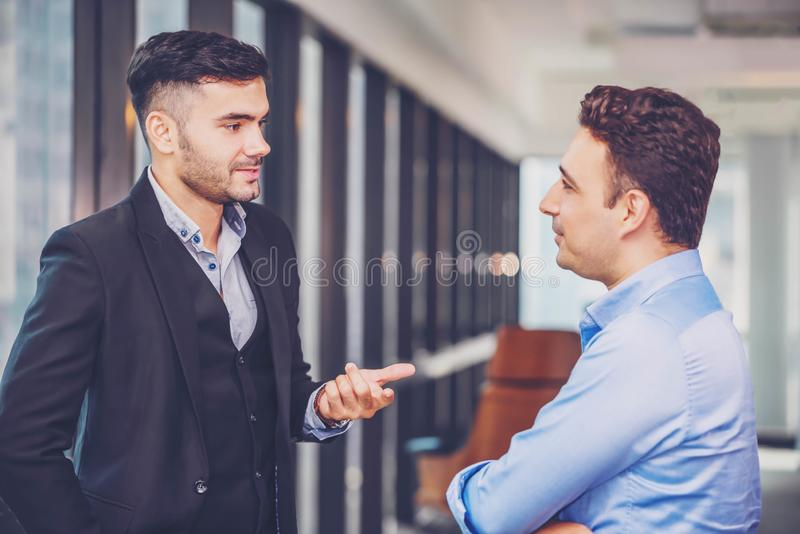 Two businessman standing and discuss a work or project strategy. Colleague talking and asking for the work opinion stock photos