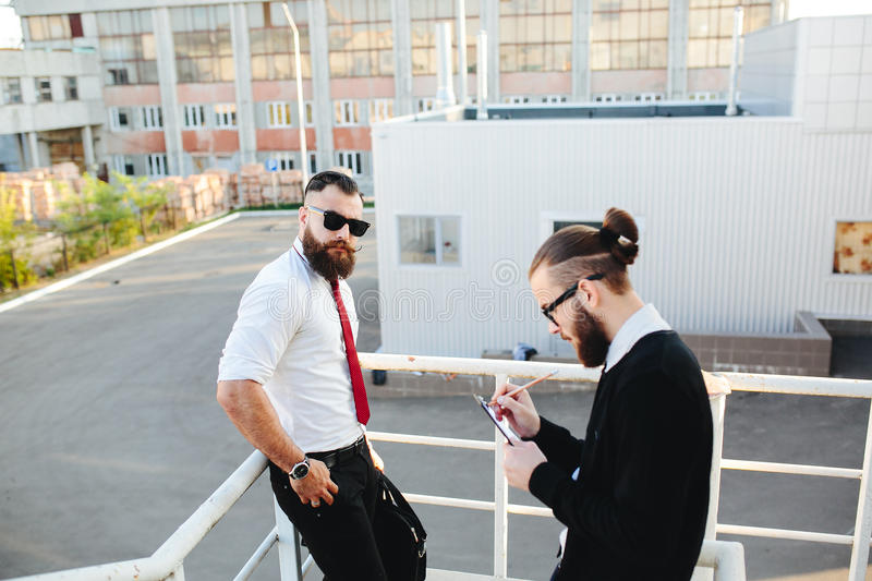 Two businessman at work. Two bearded businessman working on the street stock photo