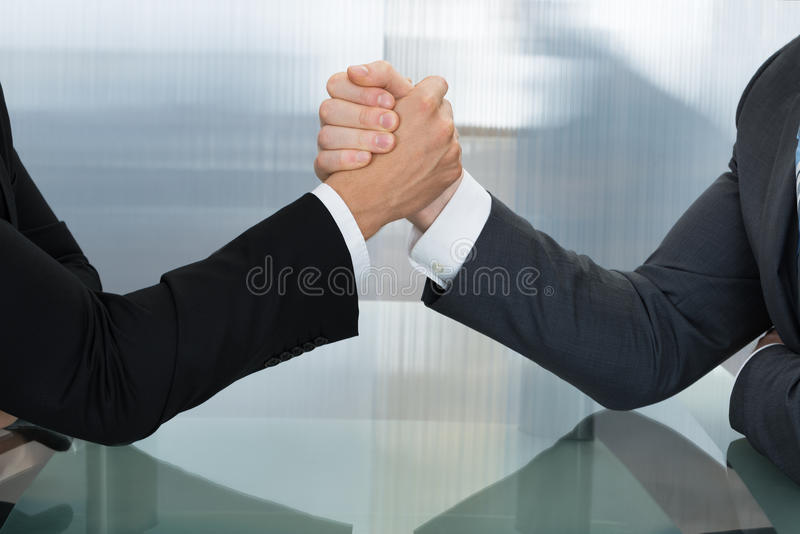 Two businessman wrestling. Two Businessman Holding Each Other Hands Over Desk In The Office royalty free stock photography