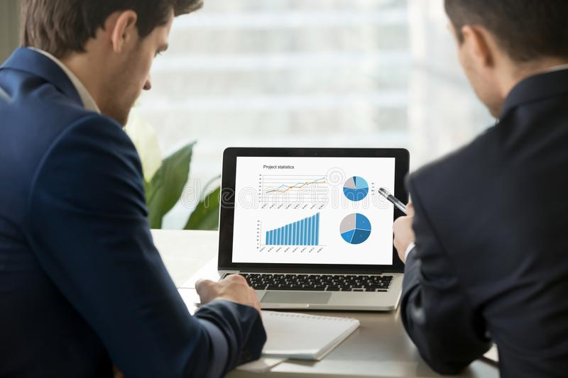 Two businessmen analyzing project statistics on laptop screen. royalty free stock photography