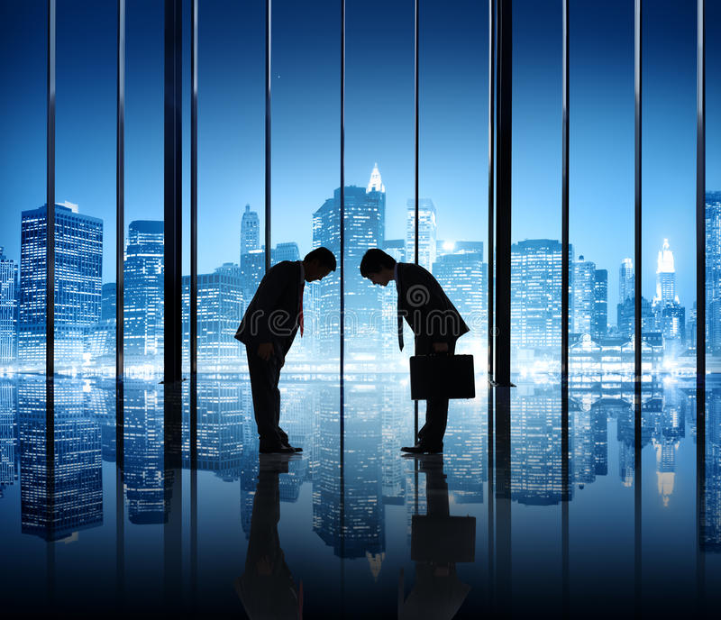Two Businessmen Bowing. To each other in an office building royalty free stock photo