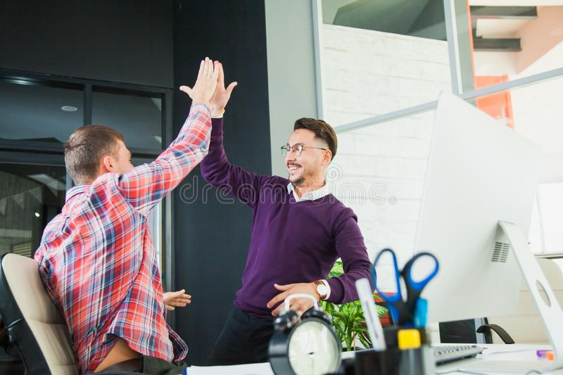 Two businessmen celebrate victory, goal reach, high five royalty free stock image
