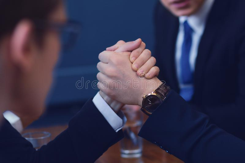 Business armwrestling in office. Two businessmen compete in armwrestling after conference. Showing business power royalty free stock photo
