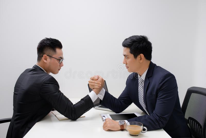 Two businessmen competing arm wrestling in office.  royalty free stock photo