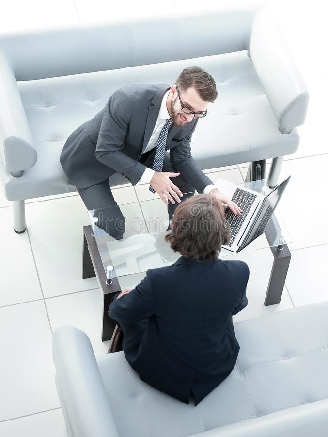 Two businessmen discussing tasks sitting at office table. View from the top.Two businessmen discussing tasks sitting at office table royalty free stock photo