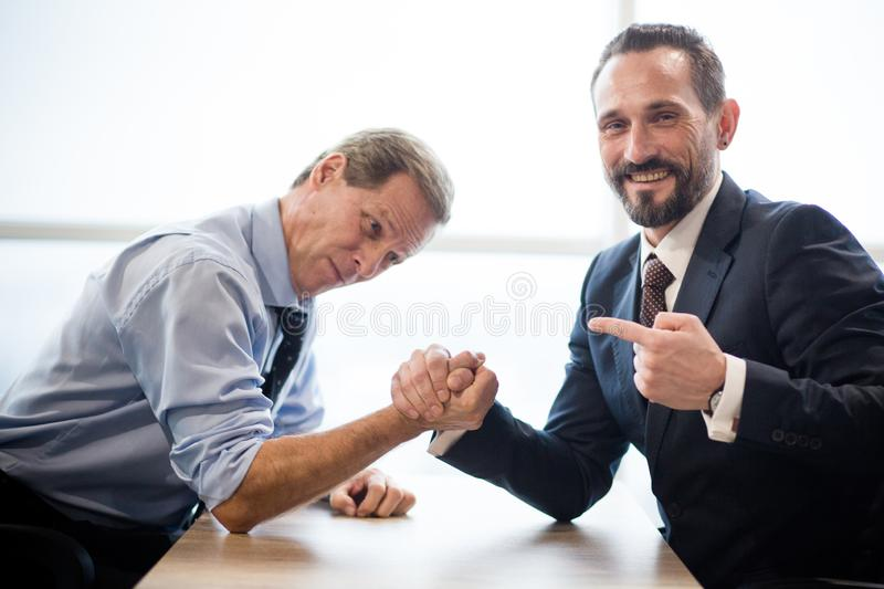 Two businessmen doing arm wrestling in office. Two Businessmen Doing Arm Wrestling. Office Interior With Big Window. Relaxing In Office Concept royalty free stock image