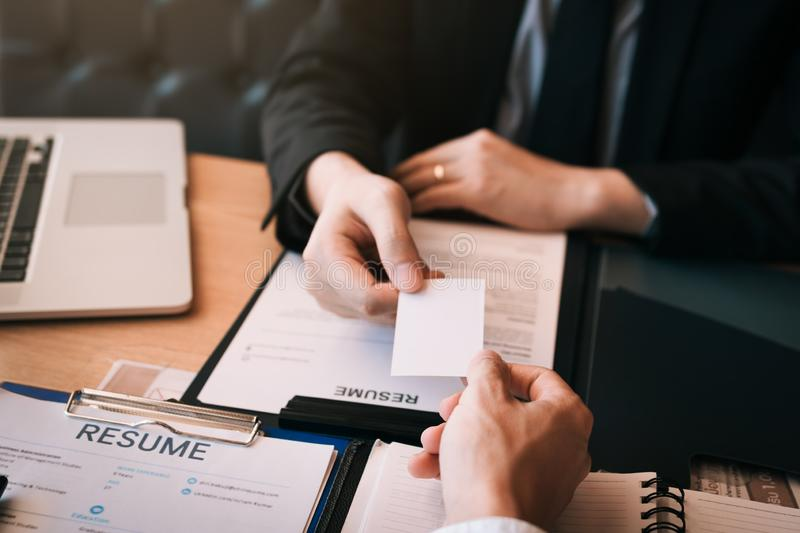 Two businessmen exchanged white business cards on a wooden table in office stock images