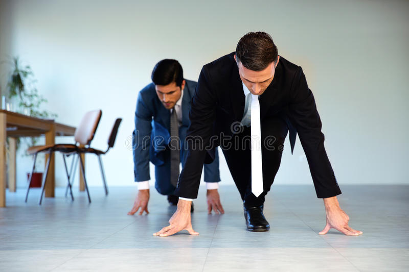 Two businessmen getting ready for corporate race stock photo