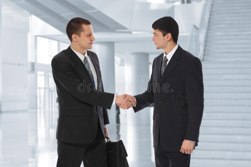 Two businessmen greet in business centre collage. Two young businessmen greet in business centre collage stock images