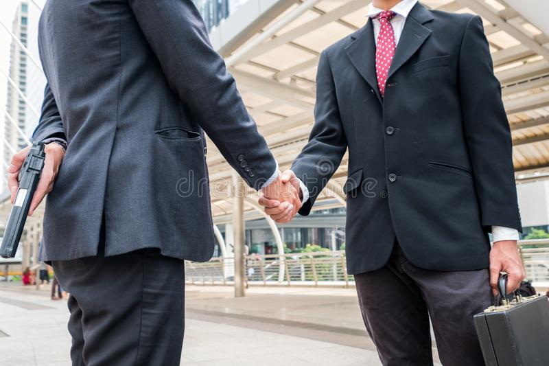 Two businessmen handshaking are dishonest and cheat with holding royalty free stock photo