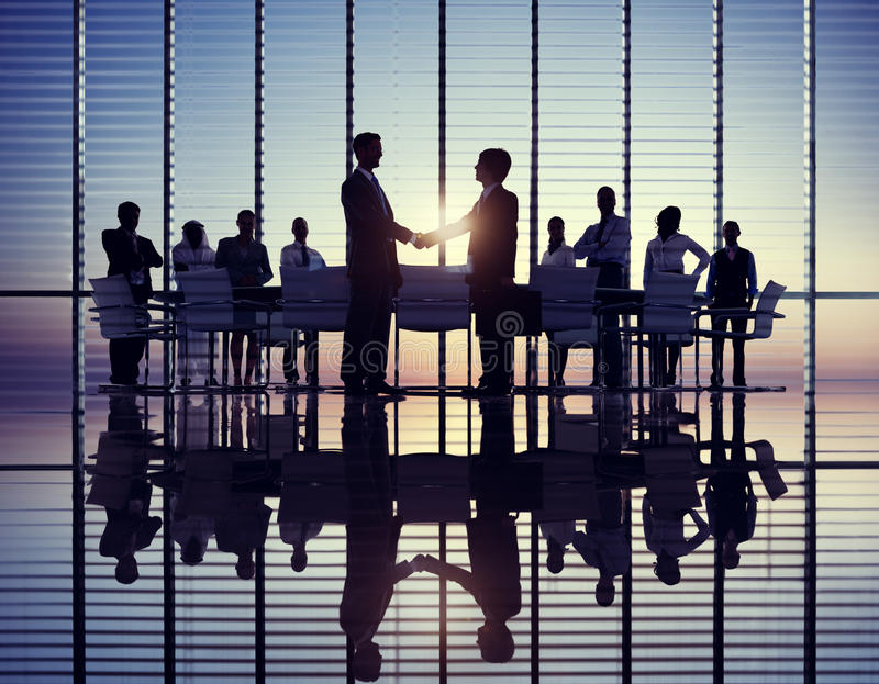 Two Businessmen Handshaking with their Colleagues.  stock images