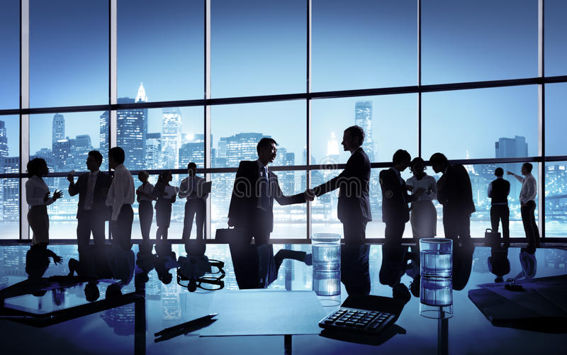 Two Businessmen Handshaking Together in the middle stock photography