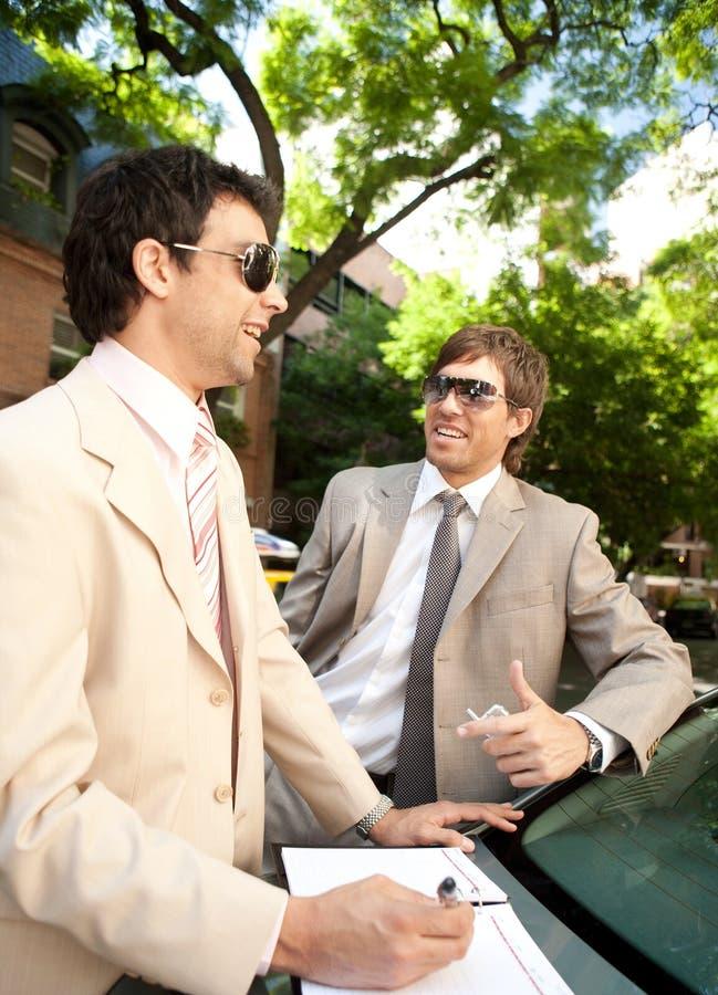 Businessmen meeting around car.