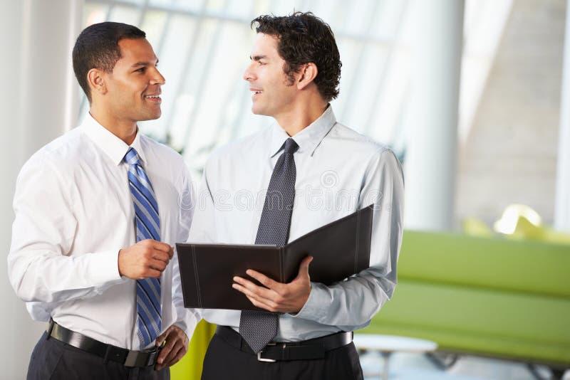 Two Businessmen Having Informal Meeting In Modern Office stock photo