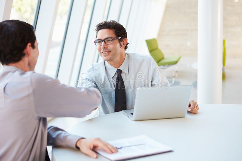 Two Businessmen Having Meeting Around Table In Modern Office. Shaking Hands royalty free stock photography