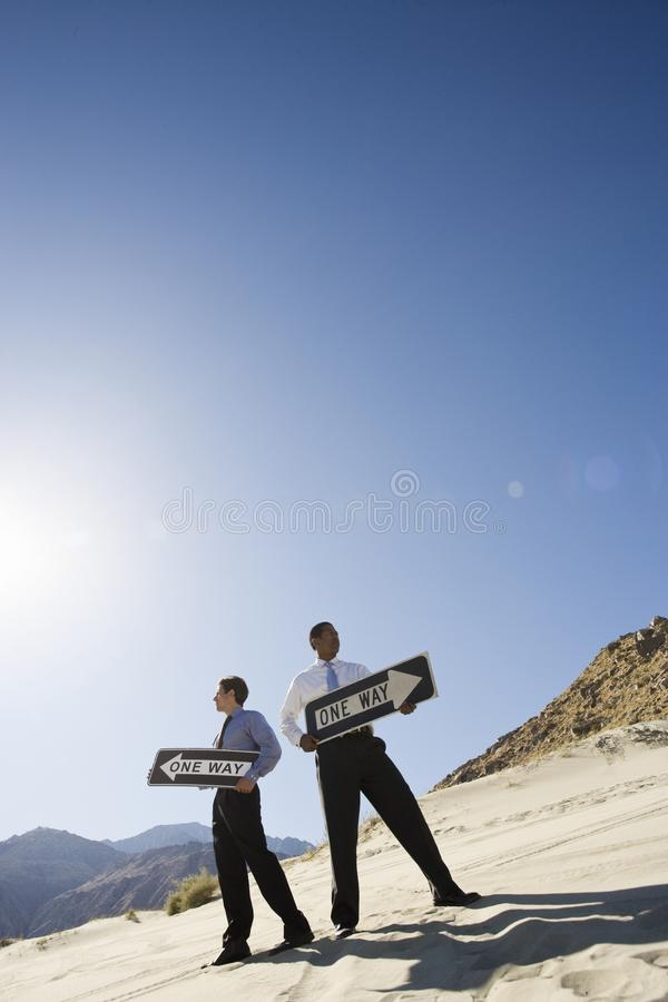 Two Businessmen Holding One Way Signs in the Desert royalty free stock image