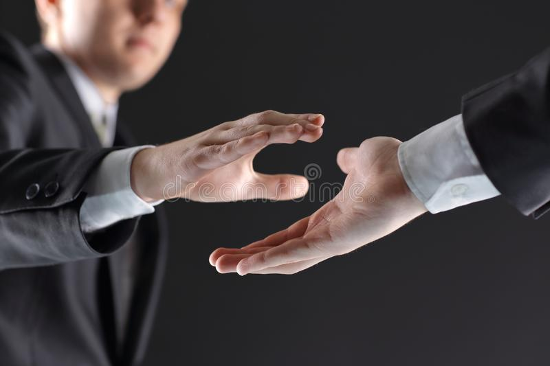 Two businessmen are holding out their hands for a handshake. royalty free stock images