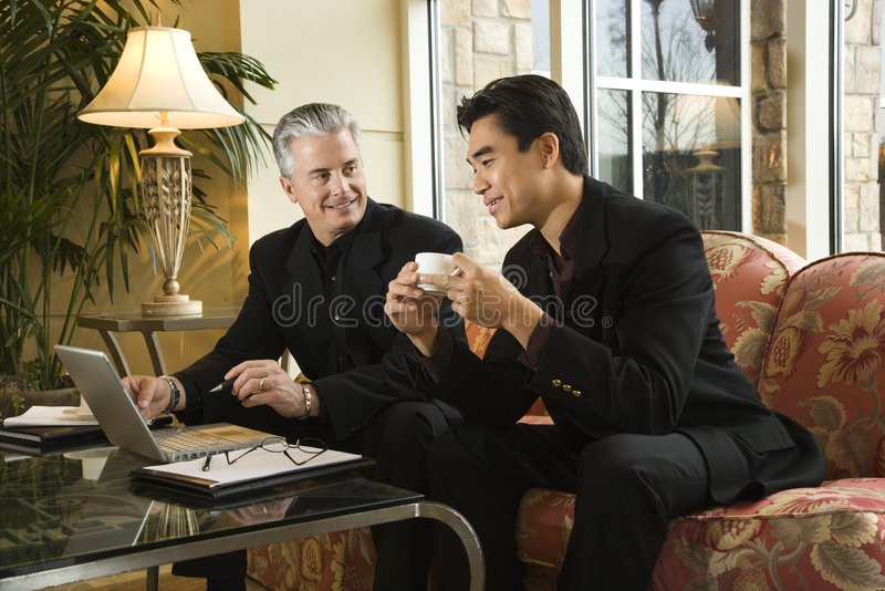 Two businessmen at hotel. Prime adult Asian and Caucasian businessmen