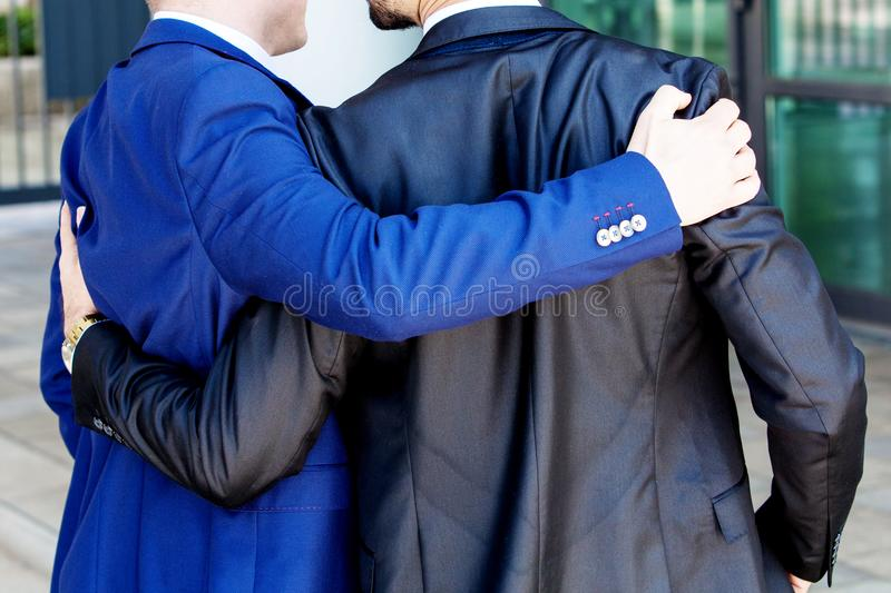 Two businessmen hugging each other outdoor stock photos