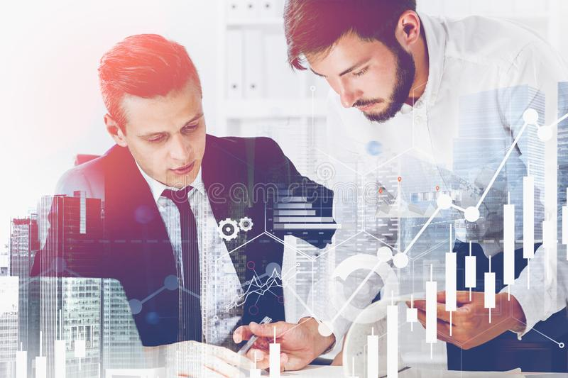 Two businessmen in office, graphs. Two serious businessmen working together in office with double exposure of cityscape and graphs. Concept of trading and stock photos