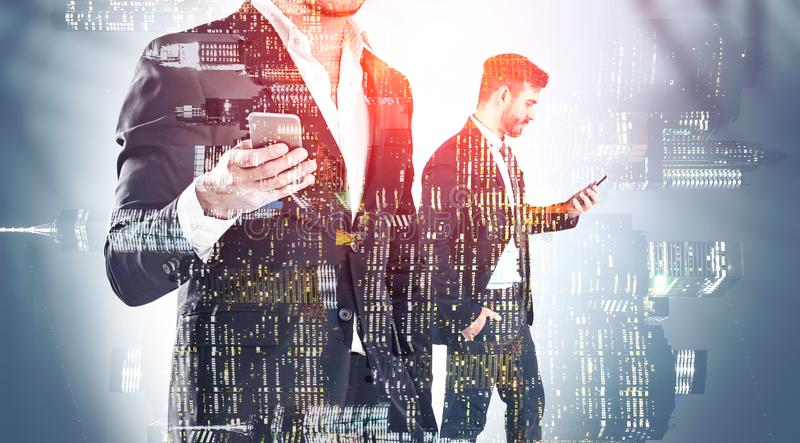 Two businessmen with phones in night city royalty free stock photography