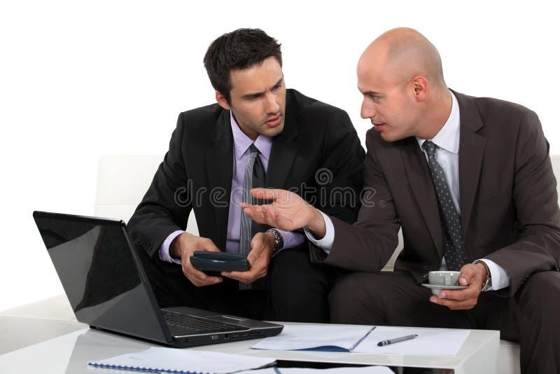 Two businessmen preparing proposal stock photos