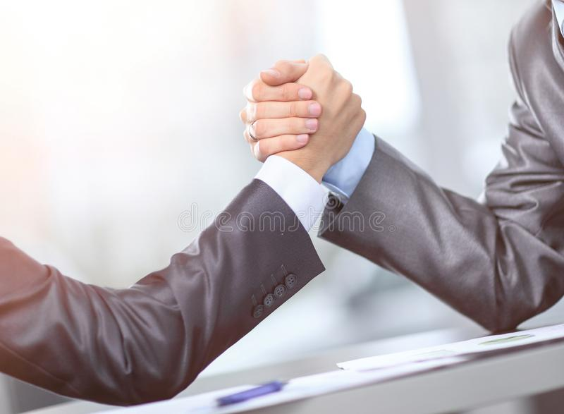 Two businessmen press hands with each other in the foreground. Fighting between entrepreneurs. Armwrestling royalty free stock photography
