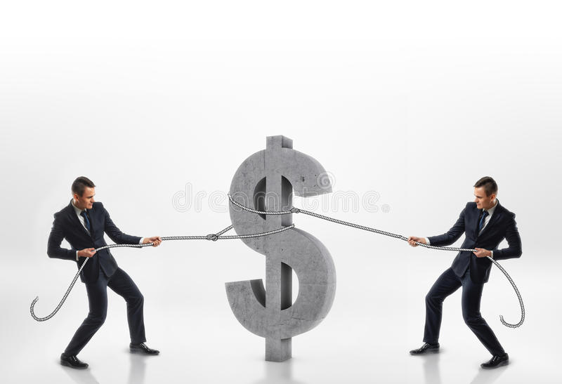 Two businessmen pulling big concrete 3d dollar sign with ropes in opposite directions isolated on white background. Rivalry and competition. Emulous workmates stock photos