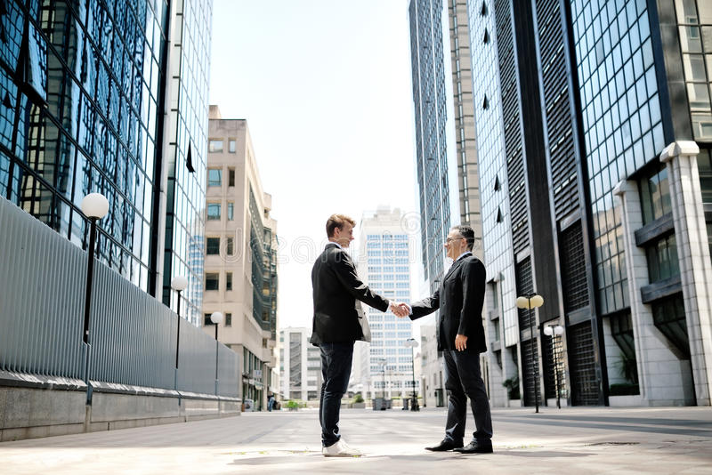 Two businessmen shaking hands on background office corporate buildings stock photography
