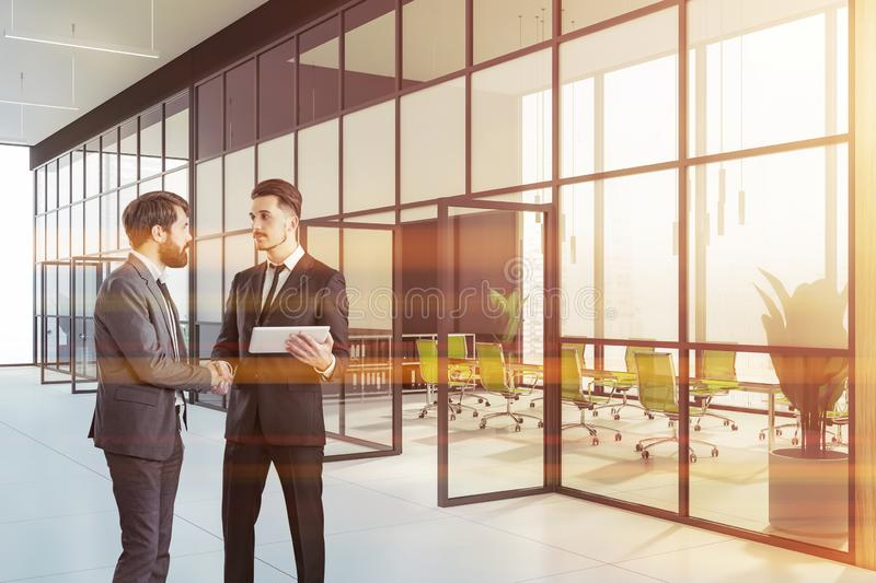 Two businessmen shaking hands near meeting room royalty free stock images