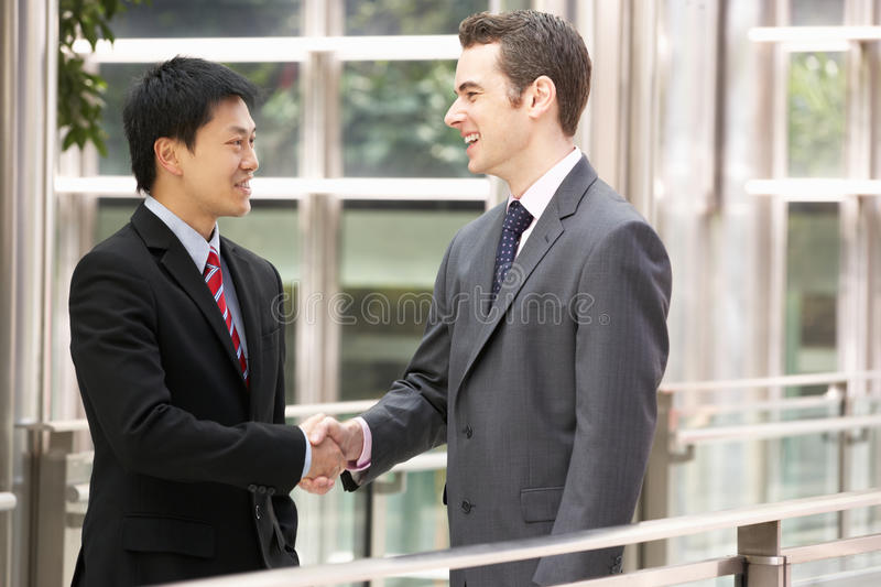 Two Businessmen Shaking Hands Outside Office. Smiling royalty free stock photo