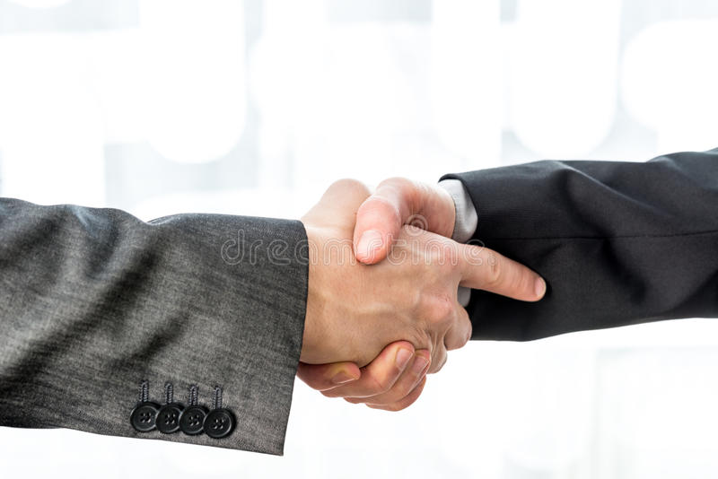 Two businessmen shaking hands over a blurred abstract background. Conceptual of a deal, agreement, partners or greeting stock images