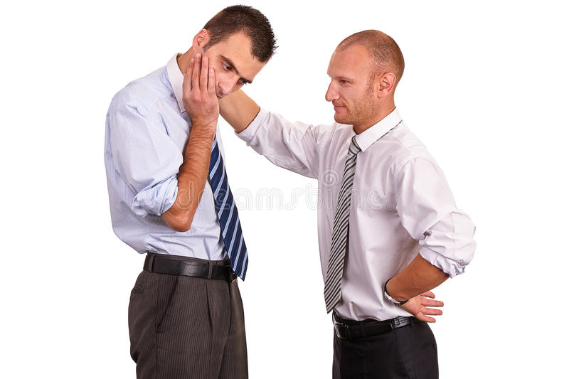 Two businessmen in shirts, troubled, one consoling, comforting a royalty free stock images
