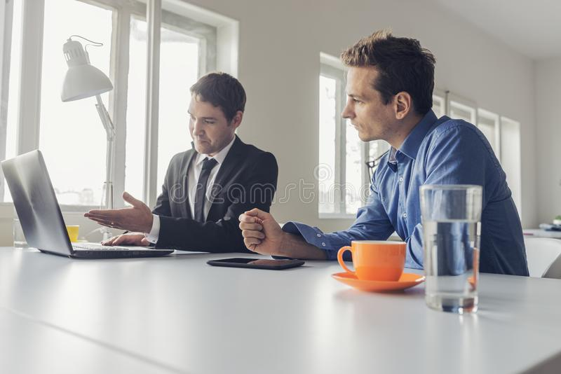 Two businessmen sitting at an office desk working together royalty free stock images
