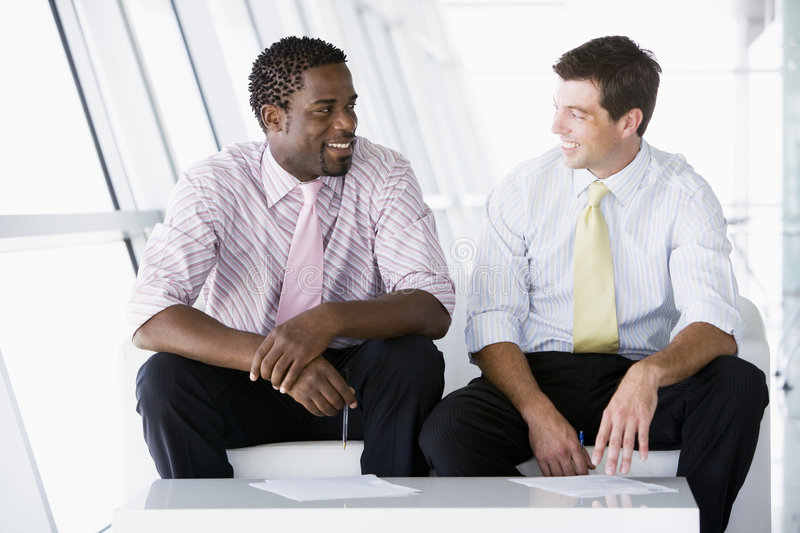 Download Two Businessmen Sitting In Office Lobby Talking Stock Image - Image: 5675179