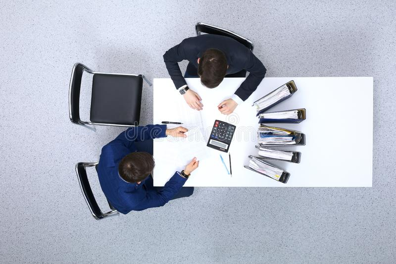 Two businessmen sitting at the table, view from above. Bookkeeper or financial inspector making report, calculating o. R checking balance. Internal Revenue royalty free stock photography