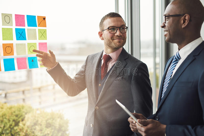 Two businessmen smiling as try to solve a problem stock photography