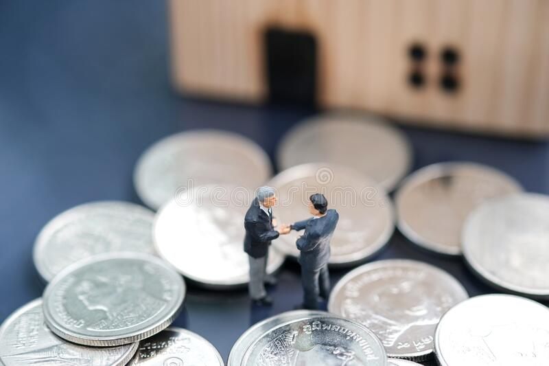 Two businessmen standing in the coin and shake hand and deal business on selling house with blurred background. Miniature people : Two businessmen standing in stock photography