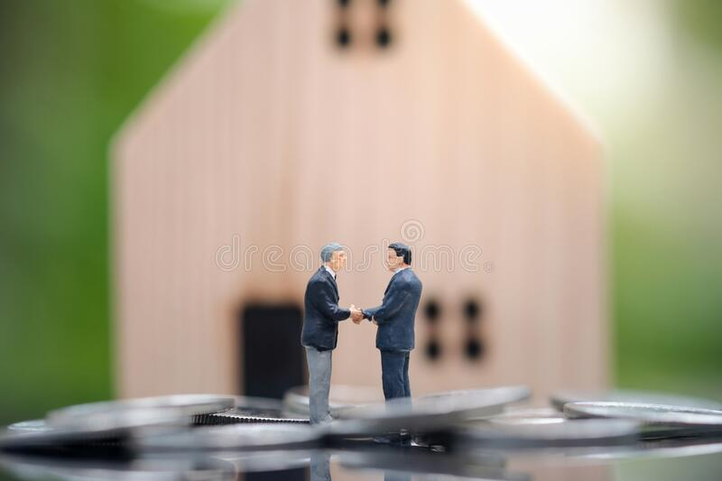 Two businessmen standing in the coin and shake hand and deal business on selling house with blurred background. Miniature people : Two businessmen standing in royalty free stock photography