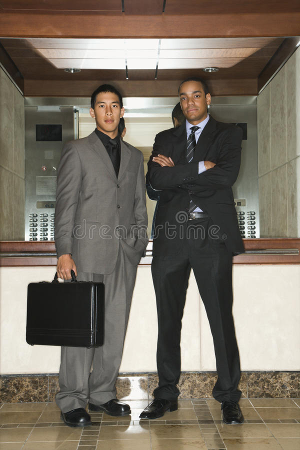 Two Businessmen Standing in Lobby stock photography