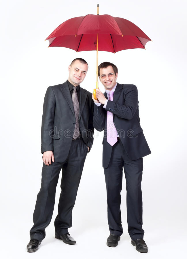 Two Businessmen Standing Under An Umbrella Royalty Free Stock Images