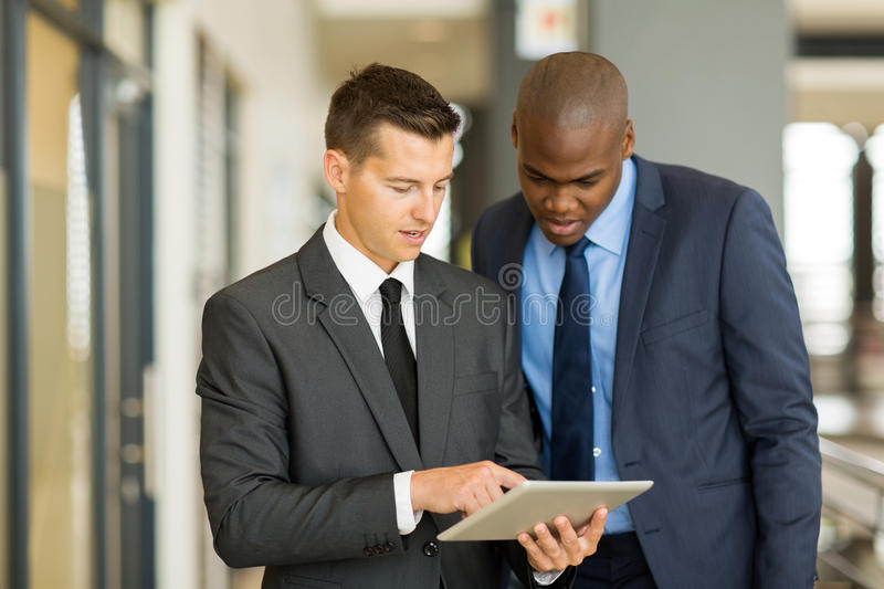 Two businessmen tablet computer. Two businessmen using tablet computer in office royalty free stock photography