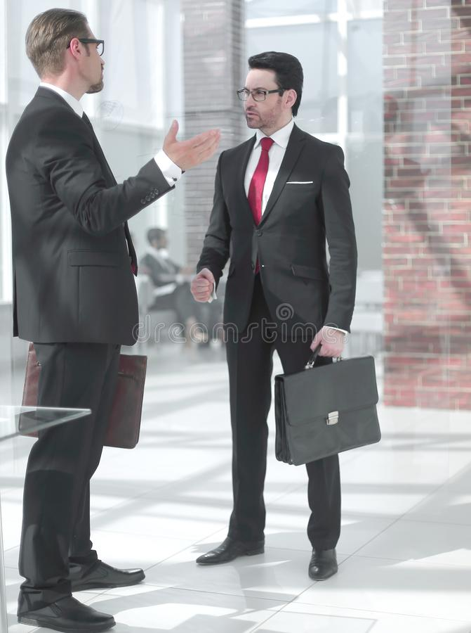 Two businessmen talking in the office hall. The concept of business relationship stock photos